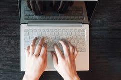La vista superior del ` s del hombre da mecanografiar en el teclado del ordenador portátil Imagen de archivo