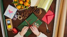 la vista superior 4K desde arriba del ` s de la señora da el adornamiento del regalo de Navidad con la cinta Foto de archivo libre de regalías