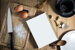 La vista superior a prepara cocinar: cuchara de madera en el cuaderno blanco y Imagenes de archivo