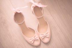 La vista superior zapatos macizos de cuero beige de las mujeres de los mediados de un talón con el arco delicado las perlas ata c Imagenes de archivo