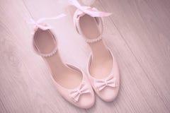 La vista superior zapatos macizos de cuero beige de las mujeres de los mediados de un talón con el arco delicado las perlas ata c Fotografía de archivo libre de regalías