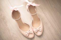 La vista superior zapatos macizos de cuero beige de las mujeres de los mediados de un talón con el arco delicado las perlas ata c Imagen de archivo libre de regalías