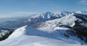 La vista superiore aerea di andata sopra la montagna nevosa dell'inverno e lo sci seguono il campo con la gente nel giorno solegg stock footage