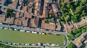 La vista superiore aerea di zona residenziale di Castelnaudary alloggia i tetti, le vie ed il canale con le barche da sopra, vecc Immagini Stock
