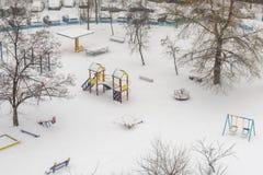 La vista superiore aerea su un parco dell'inverno con gli alberi ed il sentiero per pedoni ha coperto la neve Uomo solo che cammi Fotografia Stock