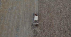 La vista superiore aerea sul raccolto sistema con il trattore funzionante video d archivio