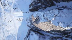 La vista superiore dal parla monotonamente una roccia coperta di neve Sulla gola della valanga dei lati fotografia stock