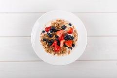 La vista superiore dei muesli del cereale fa colazione con yogurt e berrie fresco fotografia stock libera da diritti