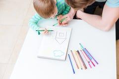 La vista superiore del disegno del figlio e del padre alloggia insieme Fotografie Stock Libere da Diritti