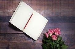 La vista superiore del foglio bianco del taccuino e delle rose rosse e rosa fiorisce sulla tavola di legno marrone rustica Copi l Immagini Stock