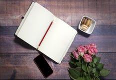 La vista superiore del foglio bianco del taccuino e delle rose rosse e rosa fiorisce sulla tavola di legno marrone rustica Copi l Fotografia Stock