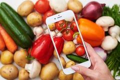 La vista superiore del telefono prende l'immagine degli ortaggi freschi Fotografie Stock Libere da Diritti