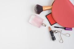 La vista superiore della borsa cosmetica rosa e compone i prodotti Immagine Stock