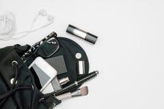 La vista superiore della borsa del nero della donna si apre con gli accessori smartphone, profumo, penne, cosmetici, trasduttore  fotografie stock