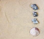 La vista superiore della raccolta delle pietre della spiaggia oscilla e coperture sopra la sabbia Immagine Stock