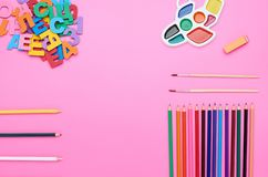 La vista superiore della tavola del bambino, la composizione dei numeri delle lettere del pennello colora la gomma di matite su u fotografia stock libera da diritti