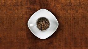 La vista superiore della tazza bianca del materiale di riempimento dei chicchi di caffè ferma il moto stock footage
