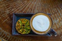 La vista superiore della tazza calda del cappuccino del caffè è servito con dolciumi tailandesi fotografia stock