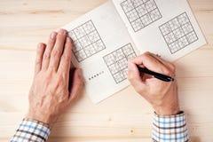 La vista superiore delle mani maschii che risolvono il sudoku imbarazza Fotografie Stock