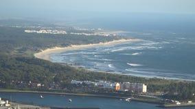 La vista superiore di bella spiaggia sabbiosa con il blu ondeggia il rotolamento nella riva, alcuni oscilla il presente portugal video d archivio