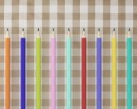 La vista superiore di molte matite variopinte disegna a matita sul plaid di tartan del tessuto Immagine Stock Libera da Diritti