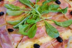 La vista superiore di pizza con bacon, olive nere ha completato con spinaci come fondo fotografia stock libera da diritti