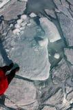 La vista superiore di un piede umano sul ghiaccio è coperta di crepe e di h fotografia stock