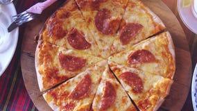 La vista superiore di una pizza con salame, macchina fotografica gira Movimento lento 3840x2160 video d archivio