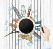 La vista superiore di una tazza di caffè e della mano disegna gli schizzi colourful delle città più famose nel mondo Il concetto  Immagine Stock