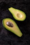 La vista superiore sul singolo avocado ha diviso a metà sul vassoio scuro Immagine Stock Libera da Diritti
