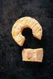 La vista superiore sulla parte ha tagliato dall'intero formaggio dorato del camembert Immagine Stock