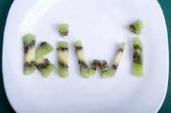 La vista superiore sulle lettere ha composto dei pezzi di kiwi Immagine Stock