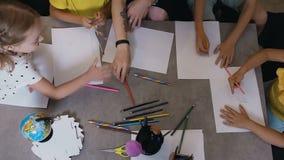 La vista superiore, un gruppo di bambini di asilo della scuola elementare che prendono le matite disegna i disegni con un insegna archivi video