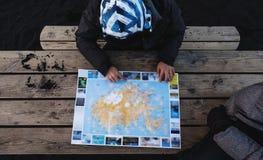 La vista superiore, viaggiatori che progettano per una vacanza scatta, facendo uso della mappa dell'opuscolo, la mappa dell'Islan Immagini Stock Libere da Diritti
