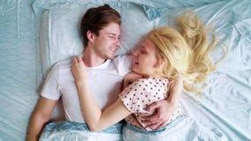 La vista superiore zumma delle coppie felici la menzogne a letto faccia a faccia di mattina video d archivio