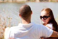 La vista trasera de los pares jovenes que se sientan en el lago echa a un lado Imágenes de archivo libres de regalías
