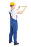La vista trasera del constructor del hombre en cinta uniforme de la medida del azul que se sostiene es imagen de archivo libre de regalías