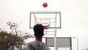 La vista trasera del jugador africano irreconocible que salta para arriba y de la bola que lanza en un aro de baloncesto, la bola metrajes