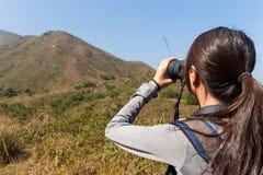La vista trasera del uso de la mujer joven del binocular Foto de archivo libre de regalías