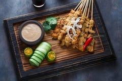 La vista vicina degli spiedi malesi del pollo - satay o sazia il ayam con la salsa dell'arachide, fondo scuro immagini stock