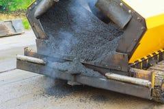 La vista vicina sui lavoratori e sull'asfaltatura lavora l'asfalto a macchina con le pale alla strada fotografie stock