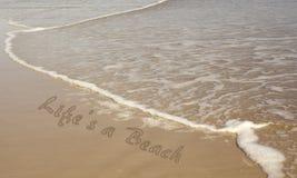 La vita è una spiaggia scritta in sabbia immagini stock