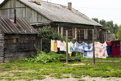 La vita del villaggio con la casa e la lavanderia di legno ha appeso sulla corda in tribunale Immagine Stock