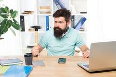 La vita dell'ufficio lo rende pazzo Uomo d'affari con la barba e baffi ammattiti con il martello in una mano Aggressivo arrabbiat fotografie stock