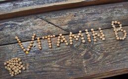 La vitamina B di parola dai piselli su una base di legno Fotografia Stock