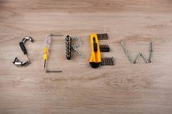 La vite di parola fatta degli strumenti differenti della riparazione mette sulla tavola di legno Immagine Stock