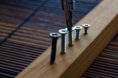 La vite sparsa ha avvitato con il cacciavite nella plancia di legno Fotografia Stock Libera da Diritti