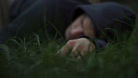 La vittima dei delinquente che si trovano sull'erba, equipaggia il cadavere, cittadino assassinato, scena del crimine immagini stock libere da diritti