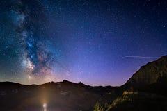 La voûte rougeoyante colorée de manière laiteuse et le ciel étoilé de la haute sur les Alpes Photo libre de droits