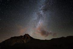 La voûte rougeoyante colorée de manière laiteuse et le ciel étoilé de la haute sur les Alpes Photographie stock